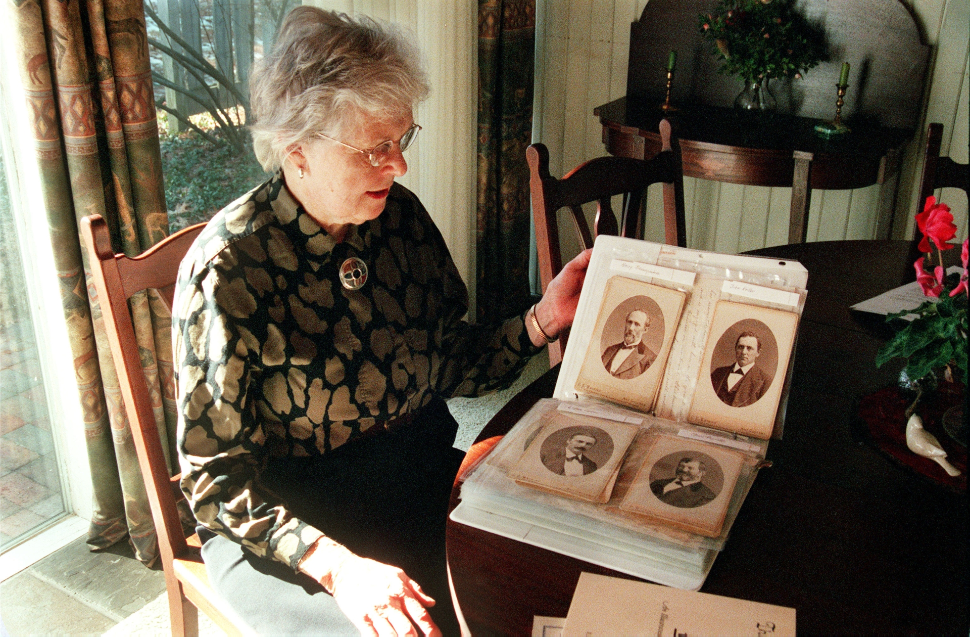 "LINCOLN, MA, USA  - 14FEB02 -Anne Brown Janes, at her home in Lincoln, Mass., has just published ""The California Excursion,"" an account of an early cross-country train trip taken by her husband's great-grandfather.  She is looking at a photo album with memorabilia from  the trip. GENEALOGY. HOBBY. PHOTO: Mary Wiltenburg / The Christian Science Monitor"